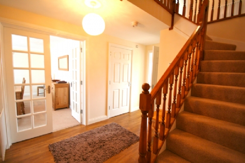 Spacious hallway with dining room and cloak room off.