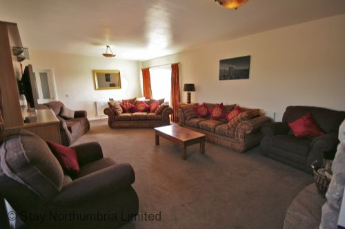 Comfortable lounge area with log burner and surround sound TV