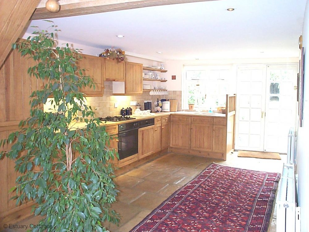 Large open plan kitchen with doors to courtyard