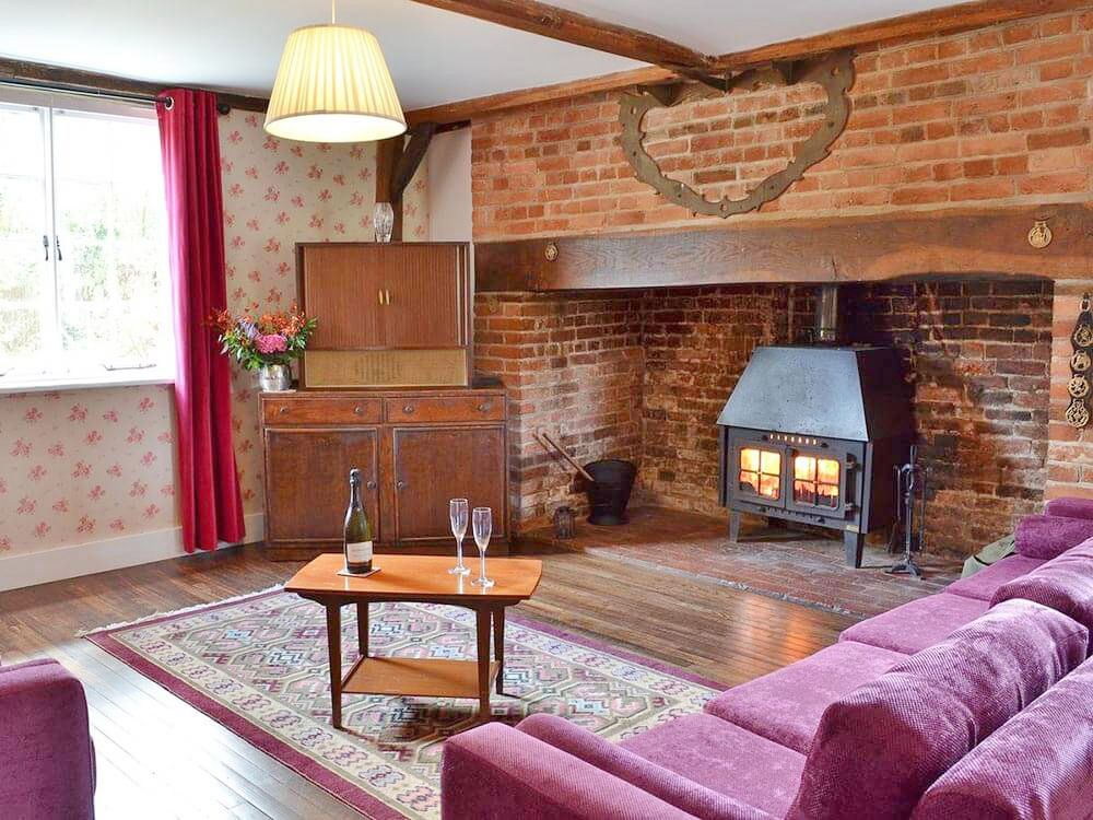 Larkin Farmhouse ground floor: Sitting area with oak floor and beams and a wood burning stove housed in a huge brick inglenook