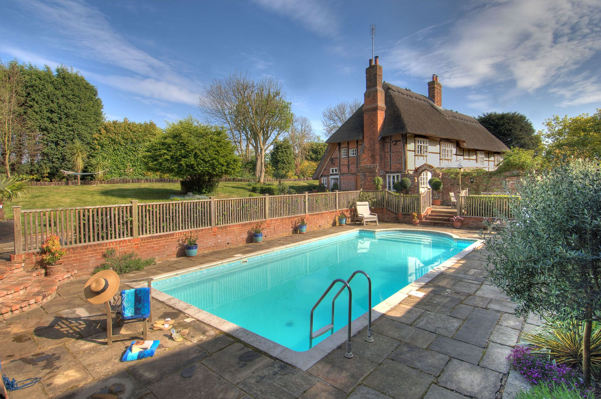 Take a dip in the fabulously warm swimming pool surrounded by a paved patio