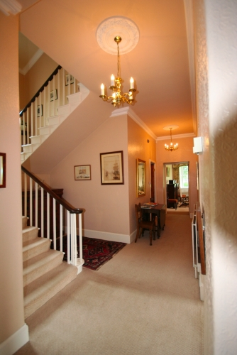 Downstair hall with sweeping double flight stairs.