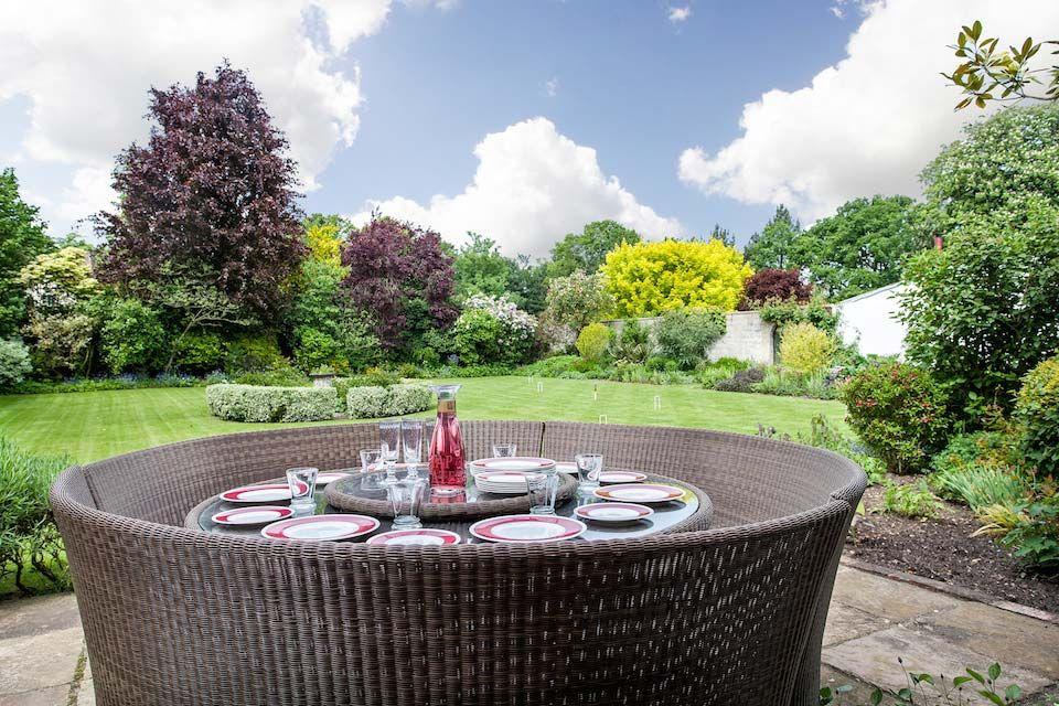 Table with circular rattan seats on the terrace in the Walled Garden, seating 10