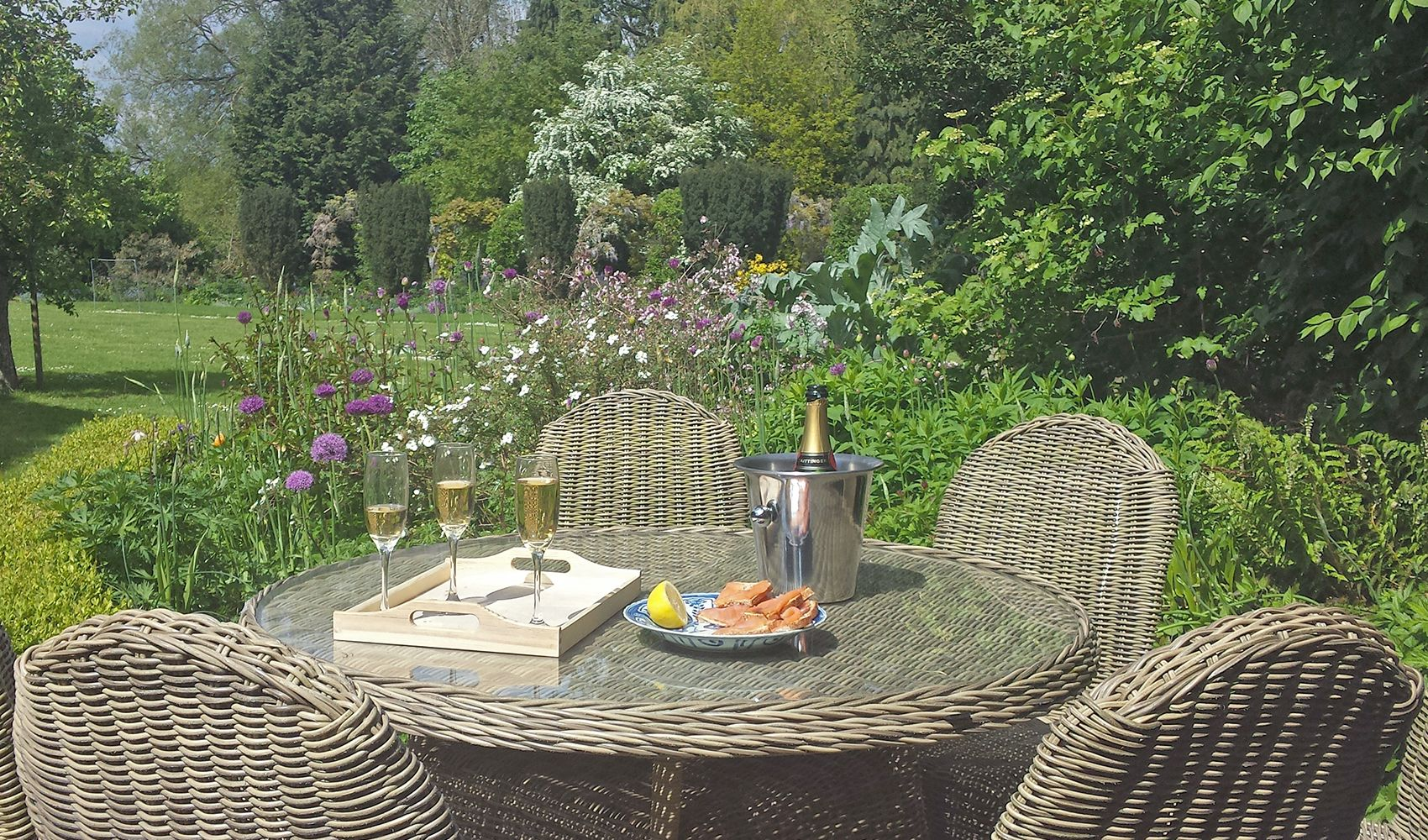 Large terrace with garden furniture and a BBQ, facing the lawn & Long Border of the walled garden