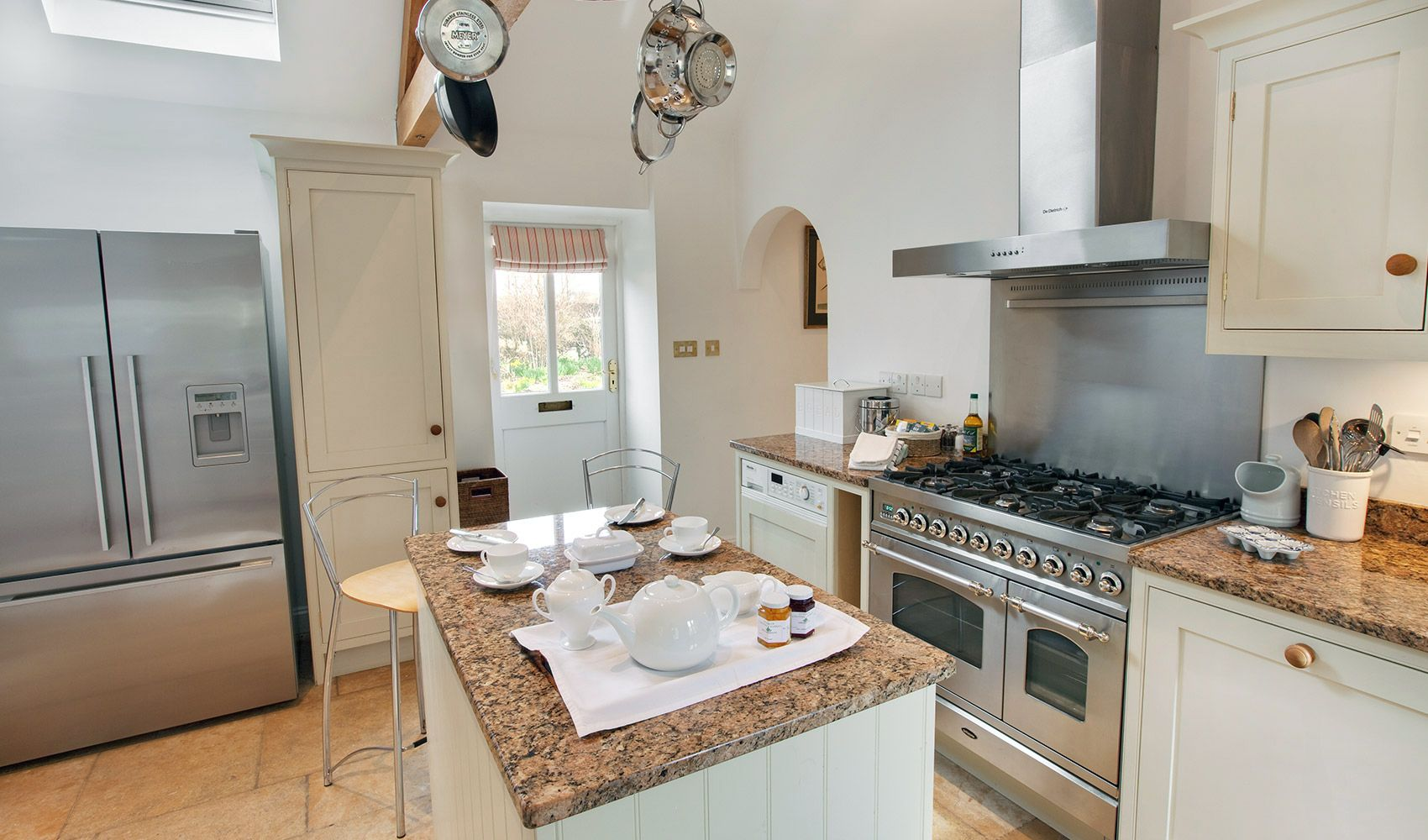 Well equipped kitchen with range cooker with double oven and 6 hobs and breakfasting bar