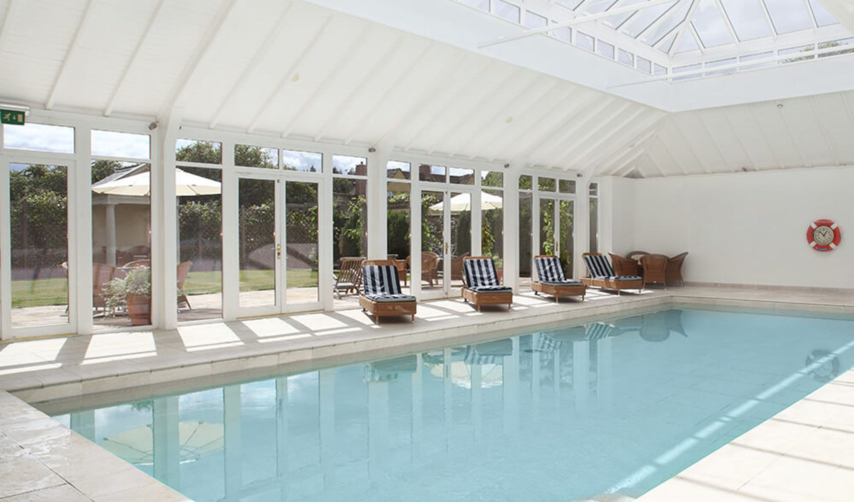 Shared indoor heated pool opening onto a beautiful garden with sun loungers