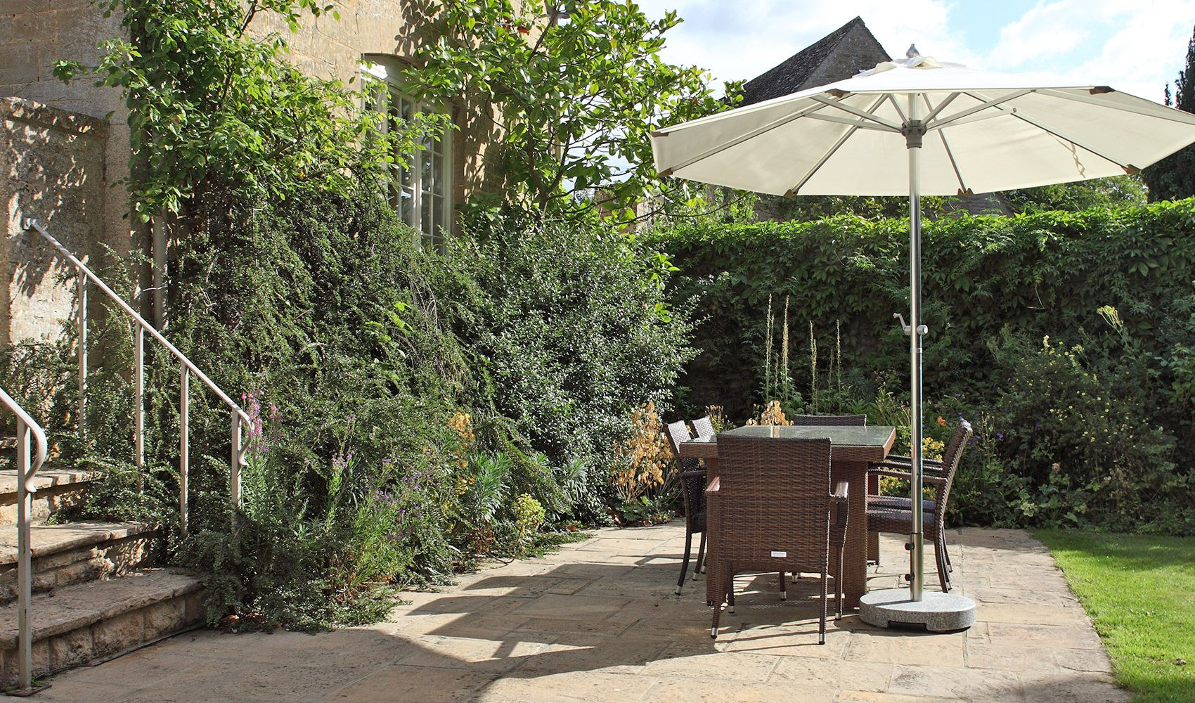 Lawned garden with terrace. outdoor dining furniture & a barbecue