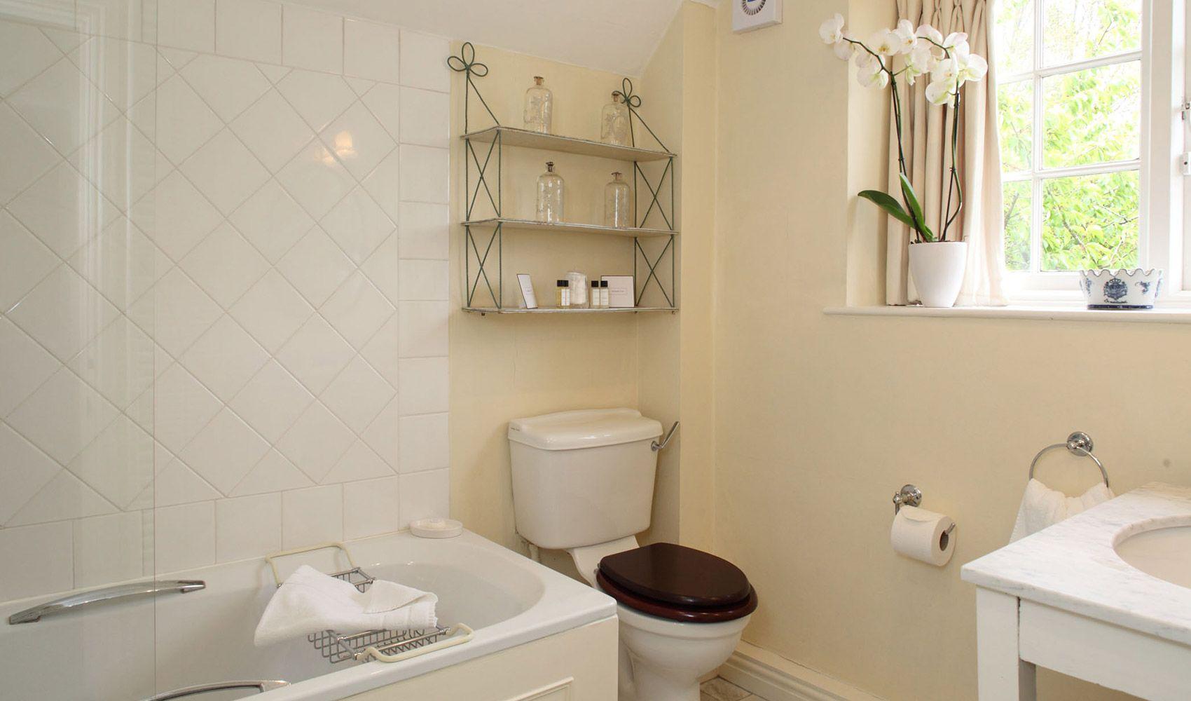 First floor: En suite bathroom to twin bedroom with shower over the bath