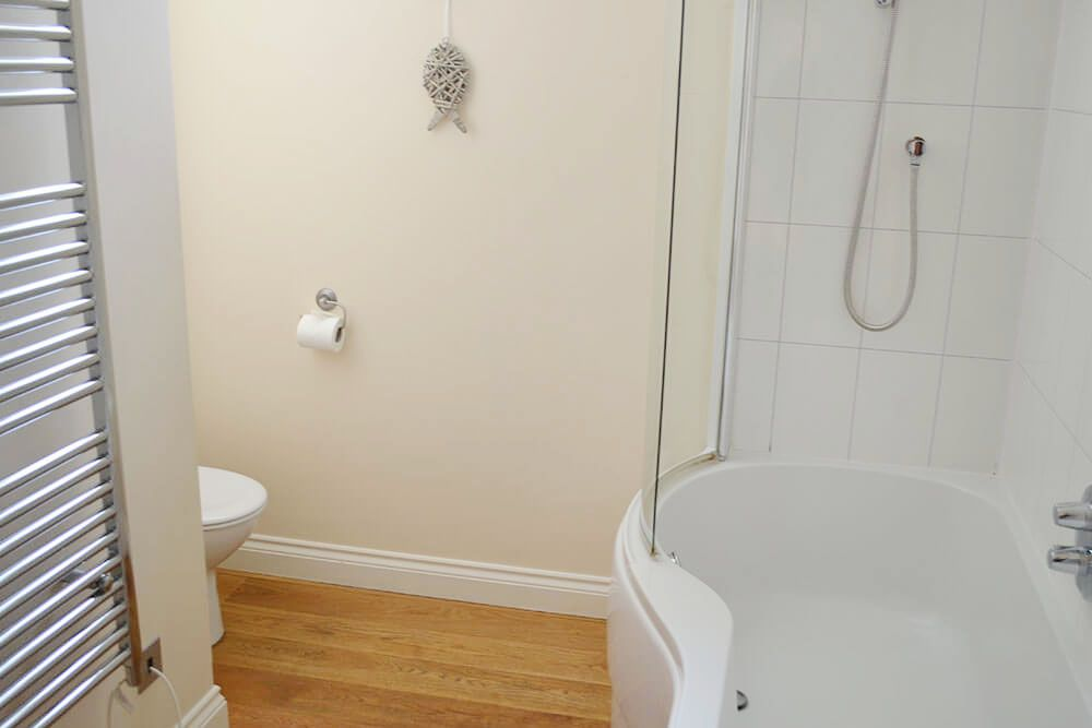 Ground floor family bathroom with a shower over the bath