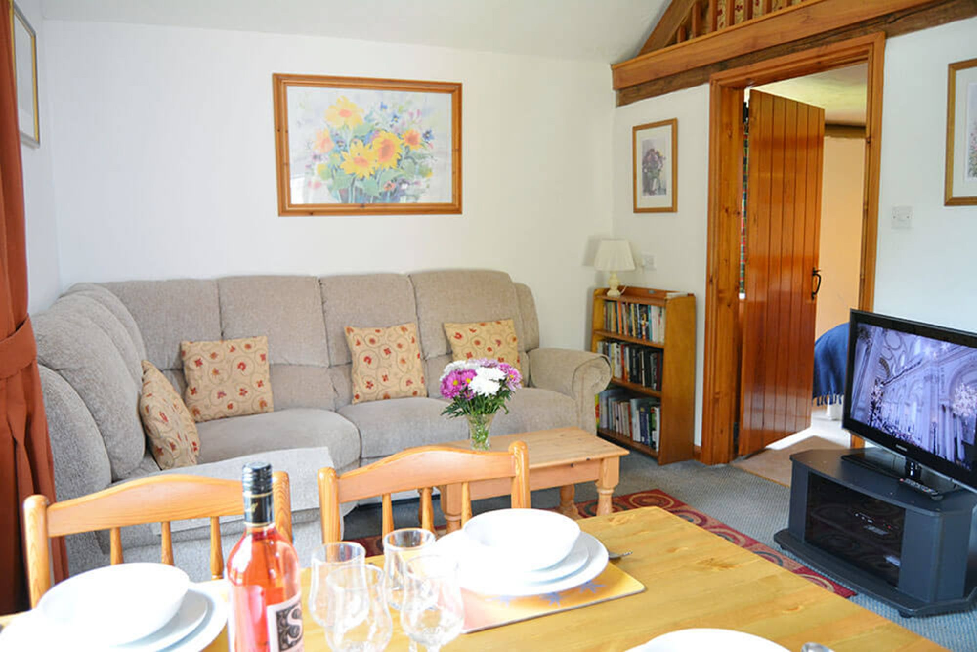 Smiddy ground floor: Spacious open plan living space comprising a sitting area with a wood burning stove, a dining area and a fitted kitchen area