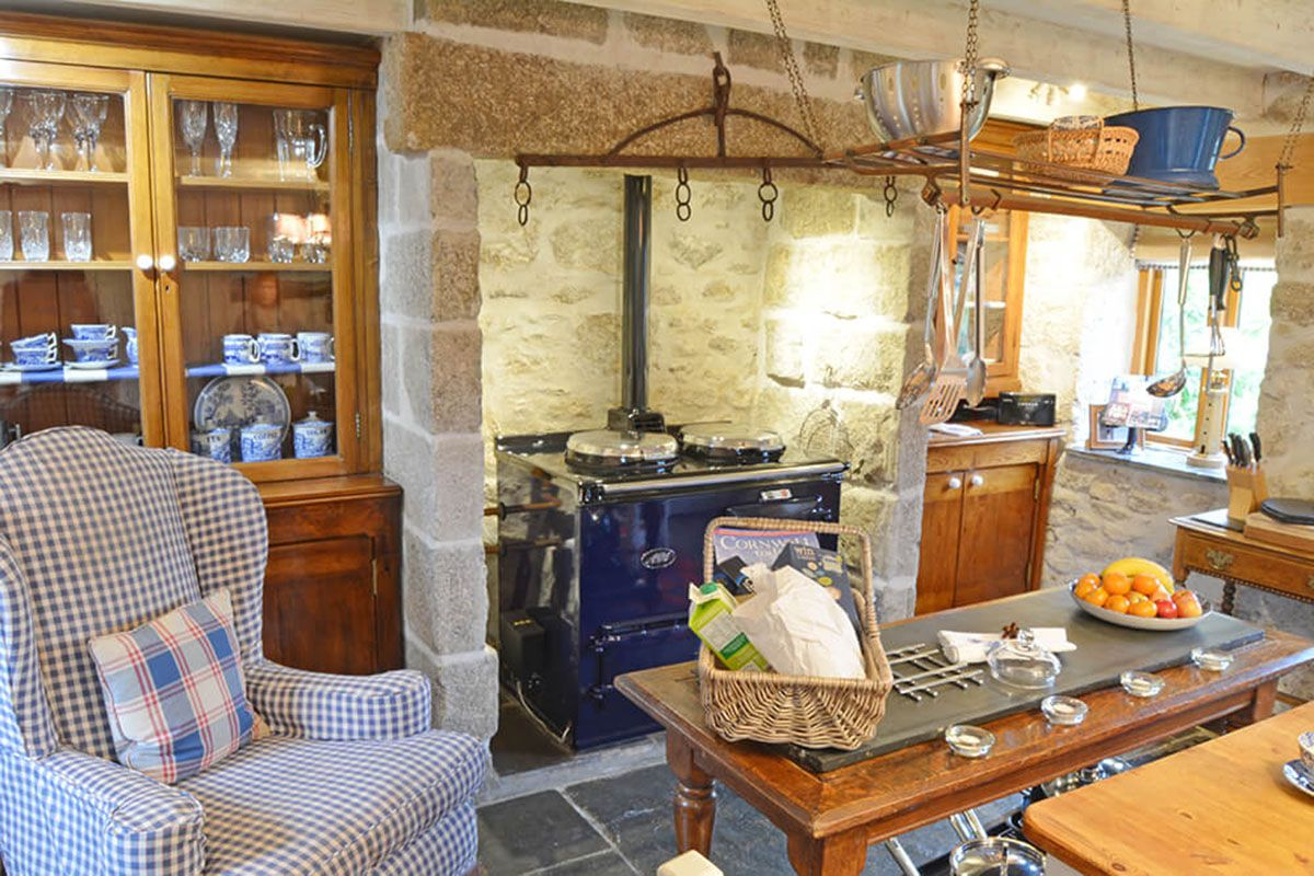 Ground floor: Farmhouse style kitchen with flagstone floor, AGA in large inglenook & dining table
