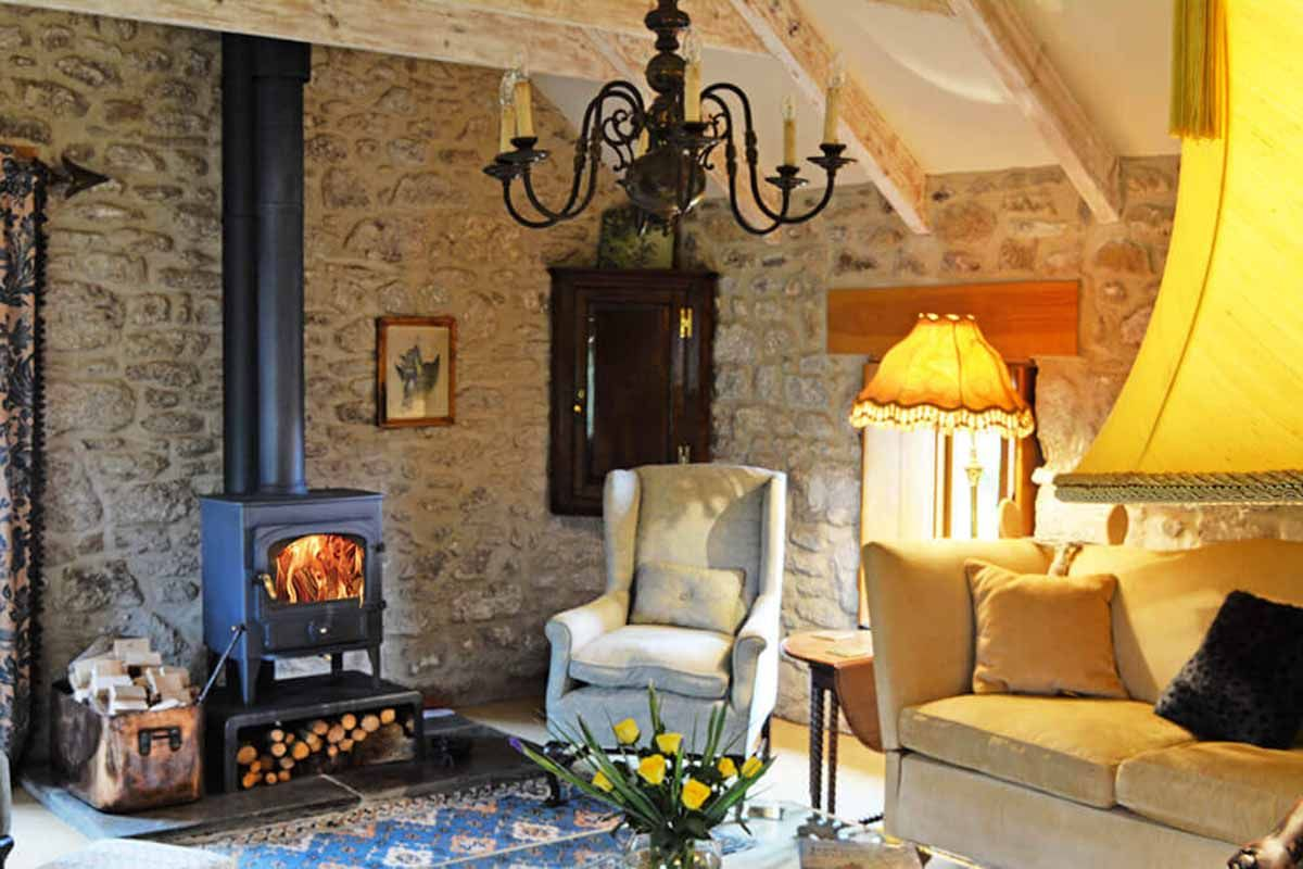 First floor: Elegant cosy sitting room with log burning stove, exposed stone walls and rafters