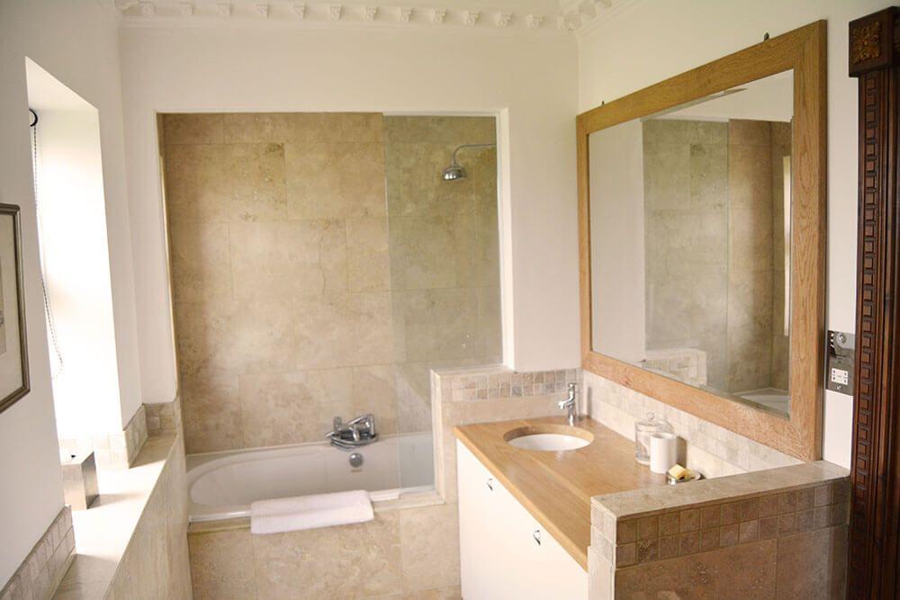 Lower ground floor: En suite bathroom to twin bedroom with shower over the bath