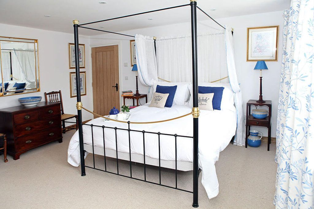 First floor: Master Bedroom with super-king brass four poster, TV and en suite walk in shower