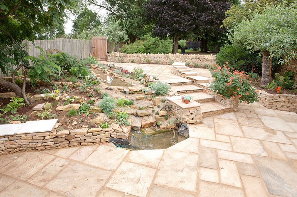 The beautifully landscaped courtyard garden has a water feature and views to the distant hills