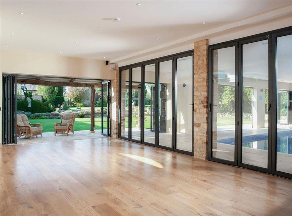 Swimming pool complex with bifold doors separating the entertainment room and the pool area