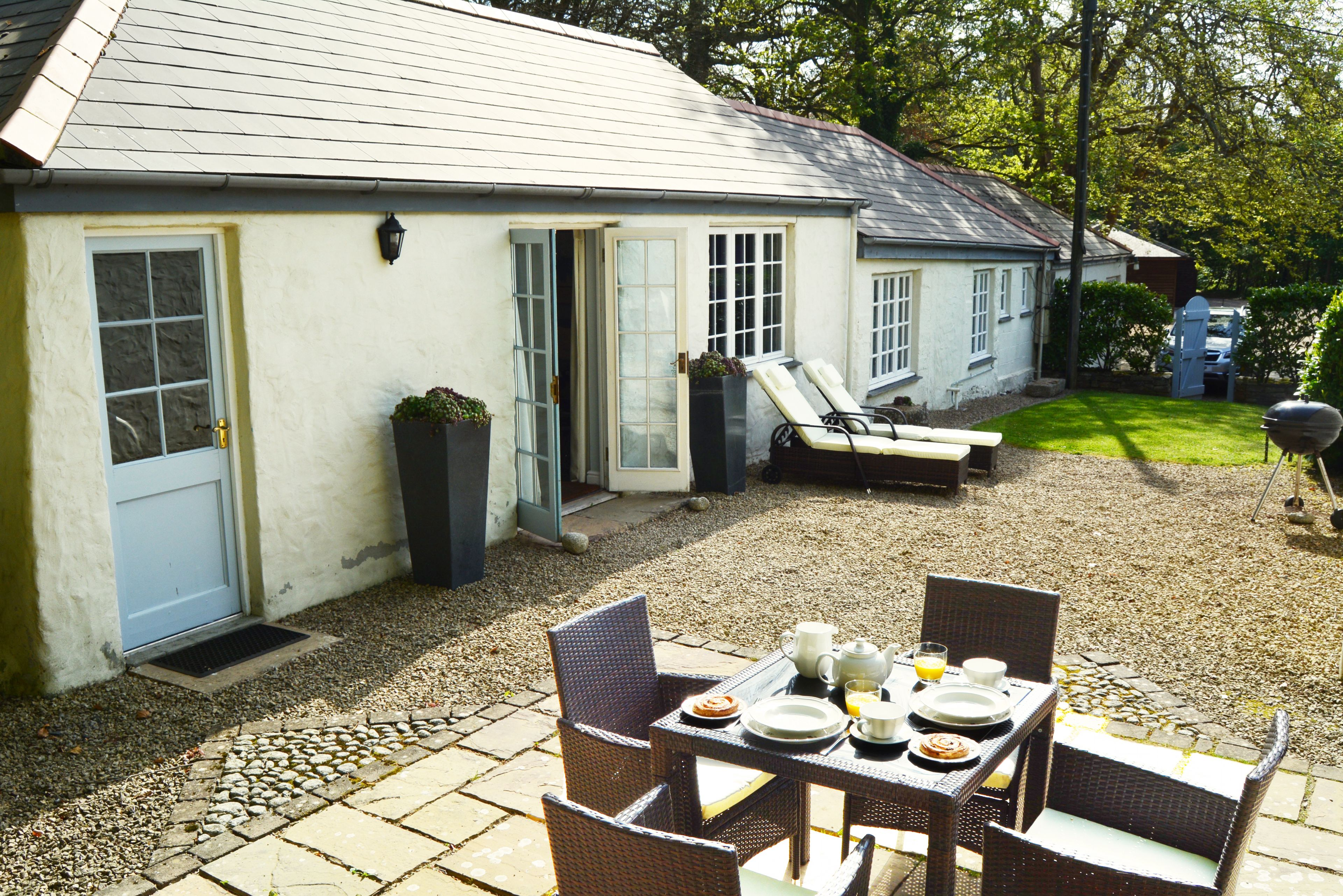 Private patio courtyard with sun loungers, garden furniture and barbecue