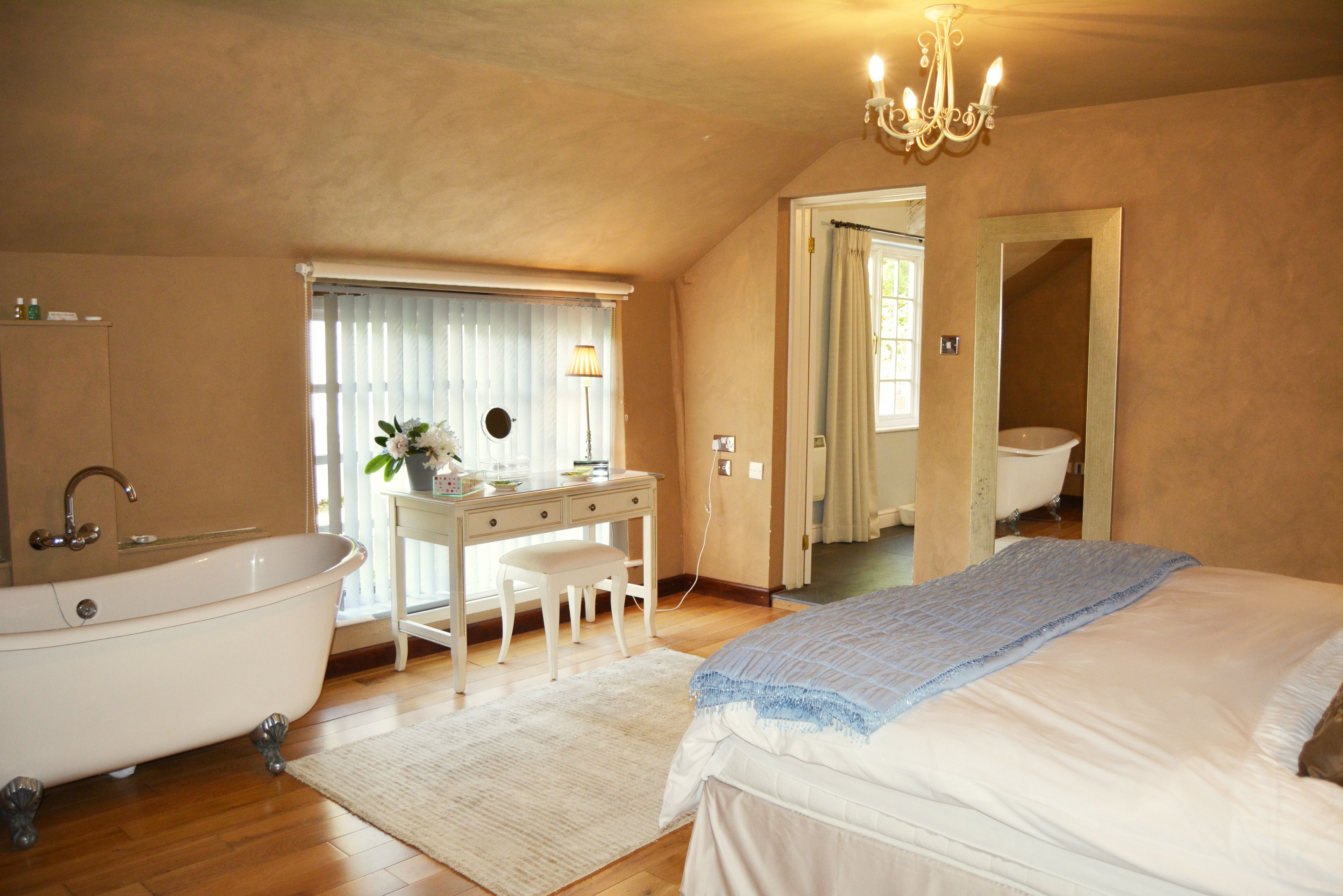 The sumptuous bedroom has a super kingsize zip and link bed and Victorian style roll-top bath