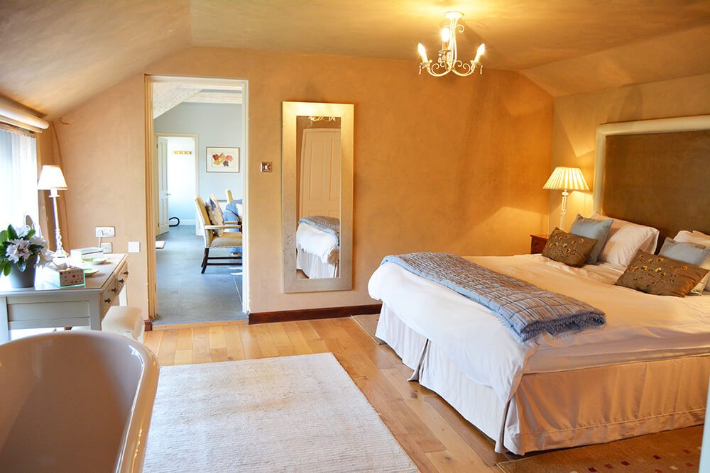 Bedroom with a super kingsize zip and link bed, a roll top bath and an en suite shower room