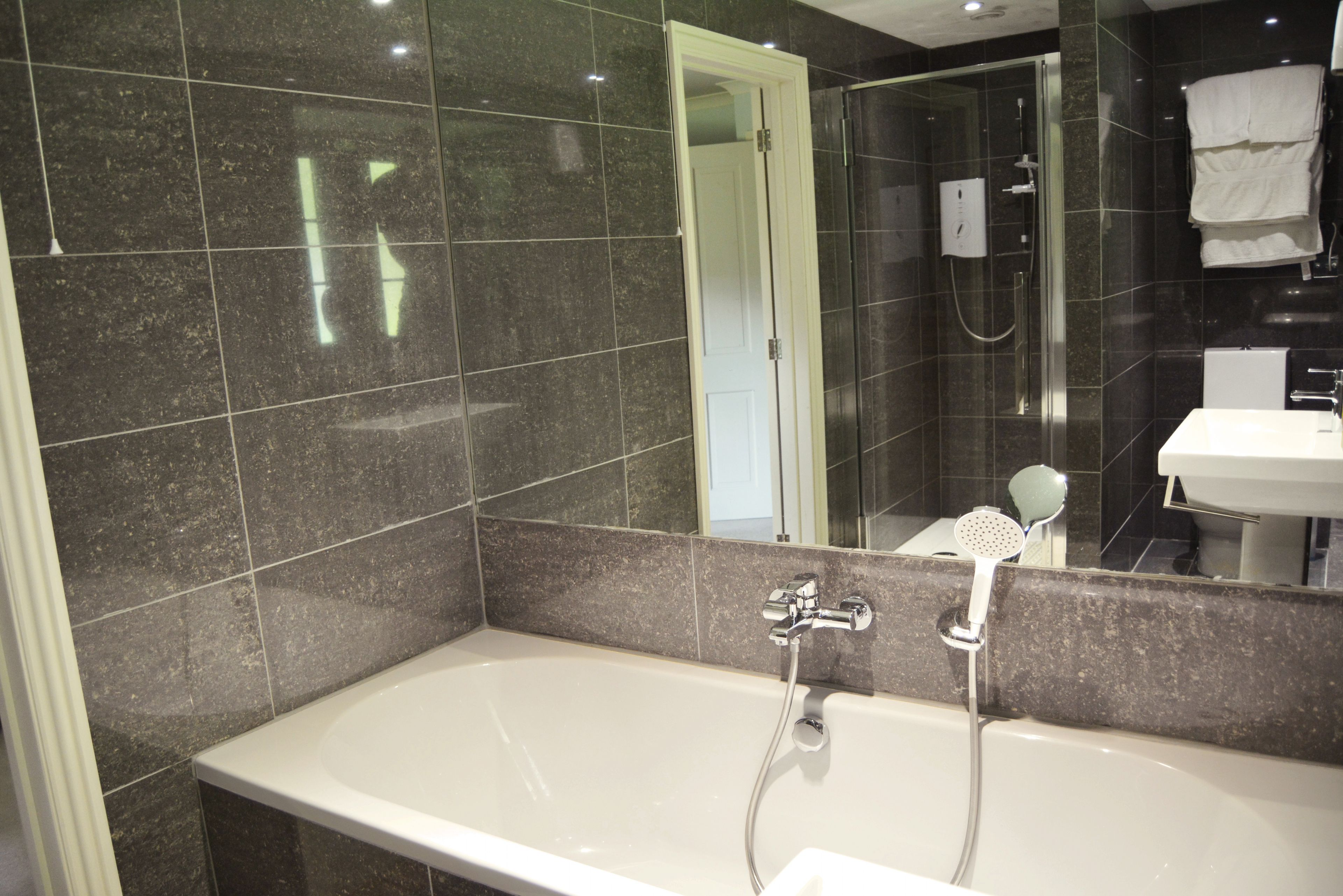 En suite bathroom with bath and separate shower to bedroom with super king size bed