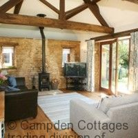 Exposed cotswold stone walls with wood burning stove and exposed beams