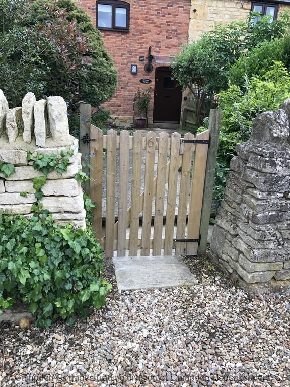 Traditional dry stone wall with wooden gate to enclosed garden