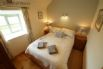 Bedroom 1 - Double bedroom with high ceiling, wooden floor, bedside table and TV