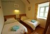 Bedroom 2 - Twin room with a TV, wooden chest of drawers and wardrobe.