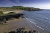 Porthor (Whistling Sands) features a cafe and white sand that actually whistles beneath your feet.