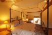 En-suite bedroom with a four poster bed and a child single bed.