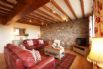 Spacious living room with exposed original beams and stone wall.