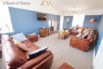 Large sitting room with corner leather settee & large wall mounted TV