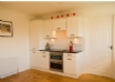 kitchen has electric oven & ceramic hob and leading through to utility area
