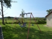 Lawned, shared play area for the children with swings and a slide.