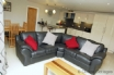 Large leather sofa situated in the kitchen/living area