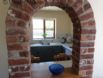 Arch shaped serving hatch between the kitchen and living area
