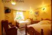 Ground floor twin bedroom with basin, TV and garden views