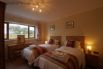Bedroom 2 (ensuite) - two large single beds, oak furniture and TV.
