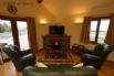 Longe area with a 50'' TV and a 3 piece leather suite