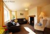 The lounge has comfy seating around a woodburner, TV and DVD